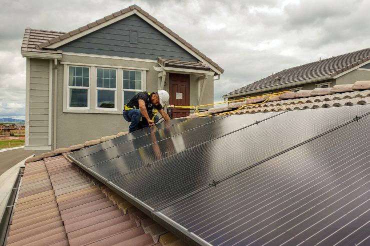 Man on Roof Working on a Solar Panel