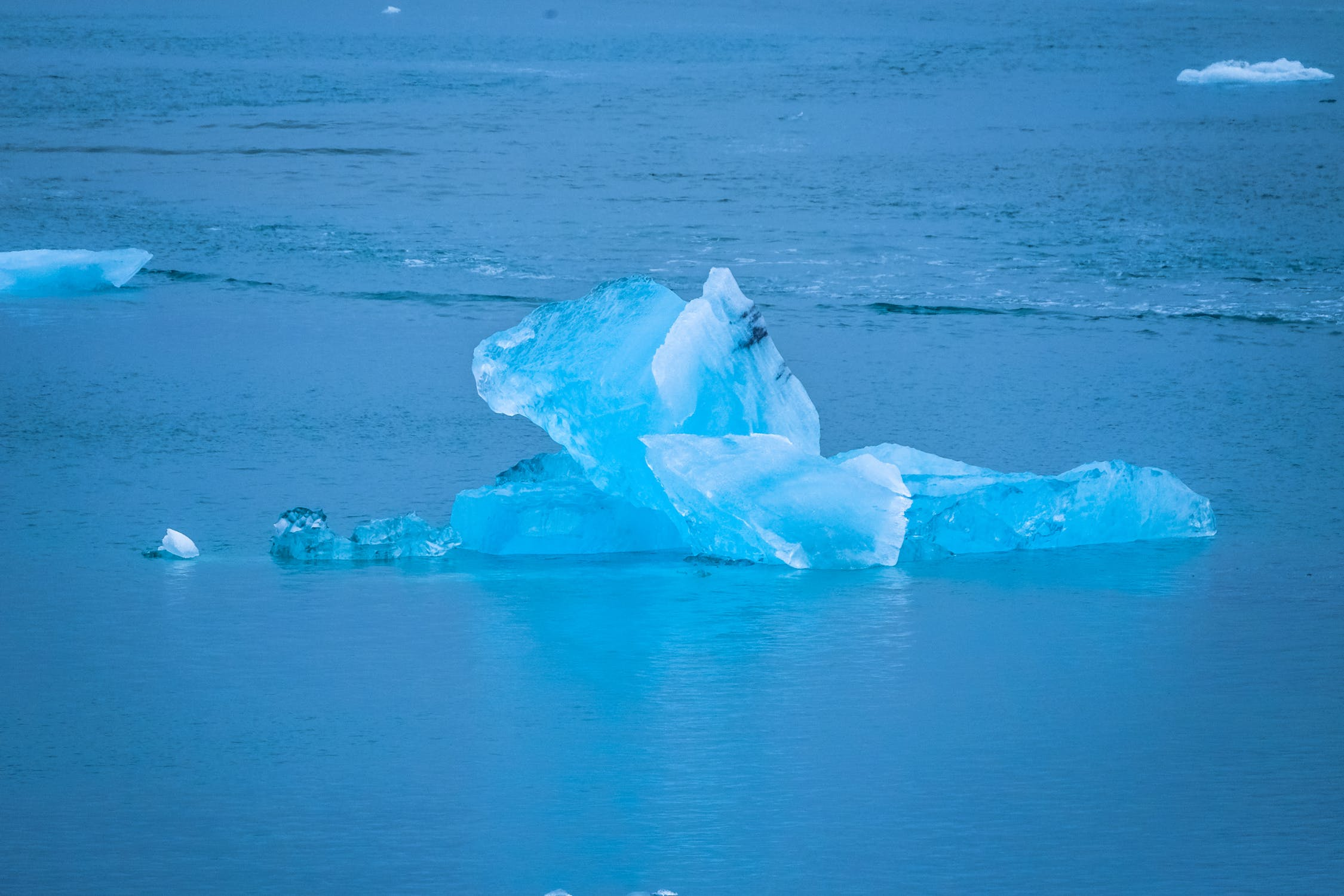small blue iceberg floating in water