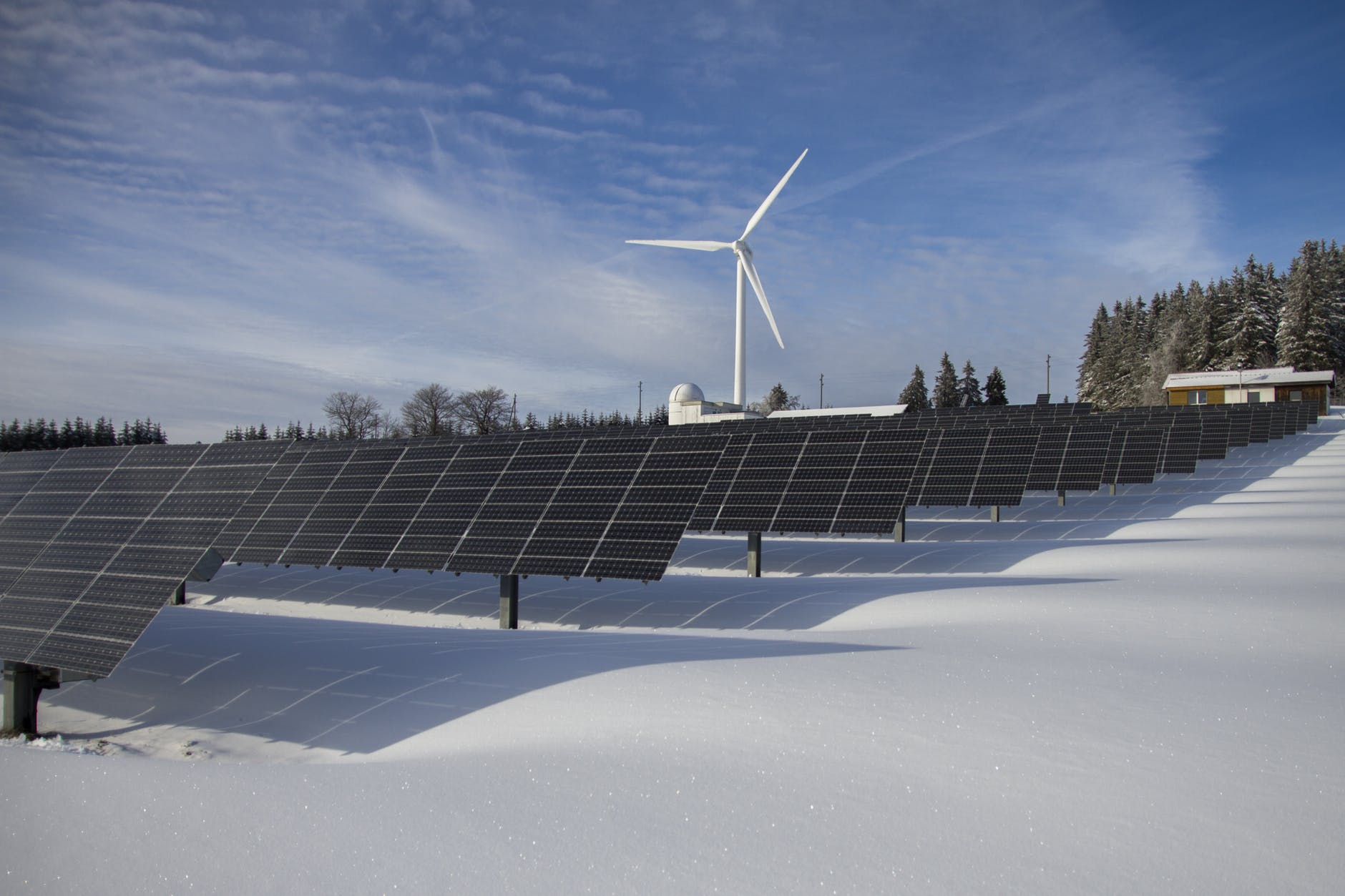 solar panels and a wind turbine in front of the snow