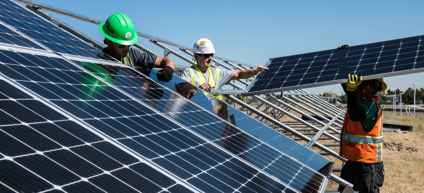 workers installing solar panels during the day